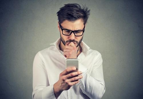 jeune-homme-naïf-ayant-des-ennuis-avec-son-smartphone-124979010.jpg